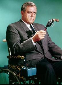 Raymond Burr sits in a wheelchair, examining a gun.
