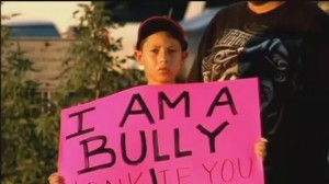 Kid holding I am a Bully sign.