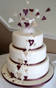 A white wedding cake with heart decorations.