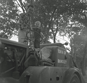 A man and a toddler stand on a half-disassembled utility vehicle under trees.
