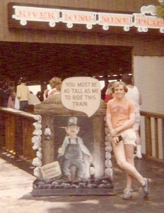 "Teen-ager leaning against a ""You must be this tall to go on this ride"" sign."