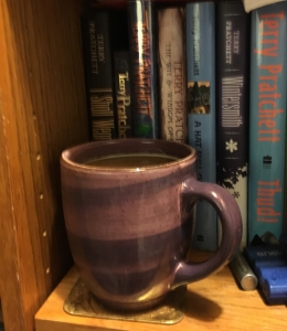 My favorite coffee mug in it's natural habitat: a bookshelf within reach of my favorite chair.