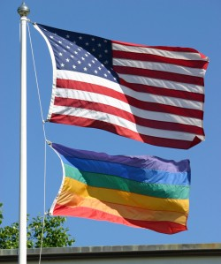 An American and a gay pride flag waving in the wind