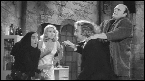 Peter Boyle as the monster, choking Gene Wilder while Marty Feldman and Teri Garr partake in an impromptu game of Charades. (© 20th Century Fox)