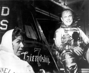 Glenn and artist Cecilia Bibby (who painted the logo on the Mercury spacecraft) sitting beside Friendship 7, the capsule that Glenn later orbited the Earth in. © NASA
