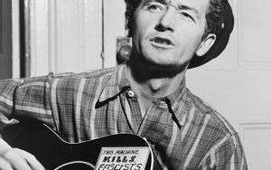 "Woody Guthrie holding his guitar infamously inscribed ""This Machine Kills Fascists"". (Creative Commons)"