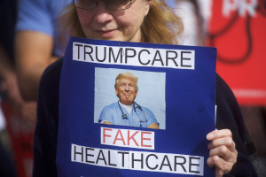 "A demonstrator holds a sign reading ""Trumpcare - Fake Healthcare"" during a health care rally at Thomas Paine Plaza on February 25, 2017 in Philadelphia, Pennsylvania.  Rallies are being held across the country in support of the Affordable Health Care Act.  (Photo by Mark Makela/Getty Images)"