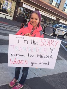 "Young girl holds say that says, ""I'm the SCARY TRANSGENDER person the Media warned you about."""