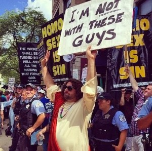 "Man dressed as Jesus stands in front of a group of anti-gay protestors. Jesus-guy holds a sign that says, ""I'm not with these guys."""