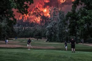 A group of men calmly golf while a giant wildfire engulfs a hill behind them.