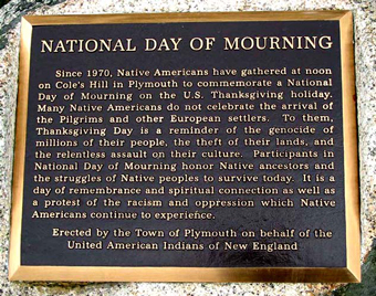 """Since 1970, Native Americans and our supporters have gathered at noon on Cole's Hill in Plymouth to commemorate a National Day of Mourning on the US thanksgiving holiday. Many Native Americans do not celebrate the arrival of the Pilgrims and other European settlers. Thanksgiving day is a reminder of the genocide of millions of Native people, the theft of Native lands, and the relentless assault on Native culture. Participants in National Day of Mourning honor Native ancestors and the struggles of Native peoples to survive today. It is a day of remembrance and spiritual connection as well as a protest of the racism and oppression which Native Americans continue to experience."""