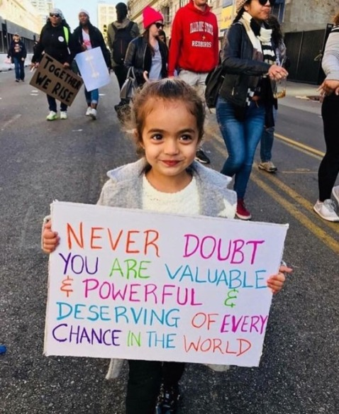 """Never doubt you are valuable & powerful & deserving of every chance in the world."" Little girl's sign quotes Hillary."