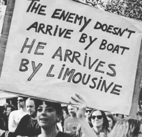 "Historical photo of a woman at a protest holding up a sign that reads: ""The enemy doesn't arrive by boat, he arrives by limousine."""