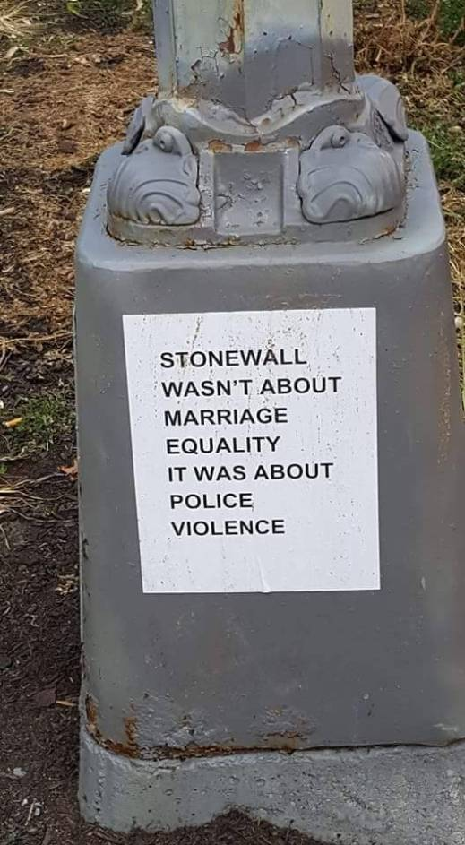 """Sticker on the base of a light pole reads, """"Stonewall wasn't about Marriage Equality, it was about police violence."""""""